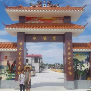 Gillian and her Auntie stand in front of the gates to her ancestral village. The gates have an eagle depicted on the left side and a waterfall depicted on the right. the gates are adorned with Chinese characters